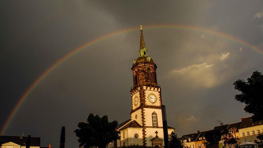 Regenbogen über Kirche